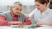 Senior woman playing checkers with a nurse in a retirement home